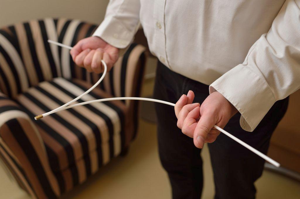 at-home Experte bei der Messung mit Wünschelrute